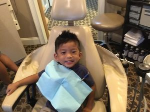 Happy young patient sitting at dental chair in Dunwoody Family & Cosmetic Dentistry.