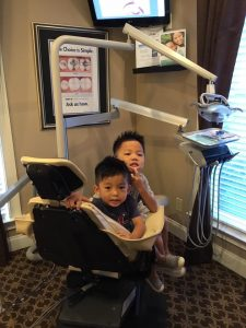 Two young boys sitting at dental chair.