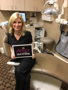 "Staff memer smiling and sitting at dental chair. She is holding a plate with inscription: ""Queen of oral hygiene""."